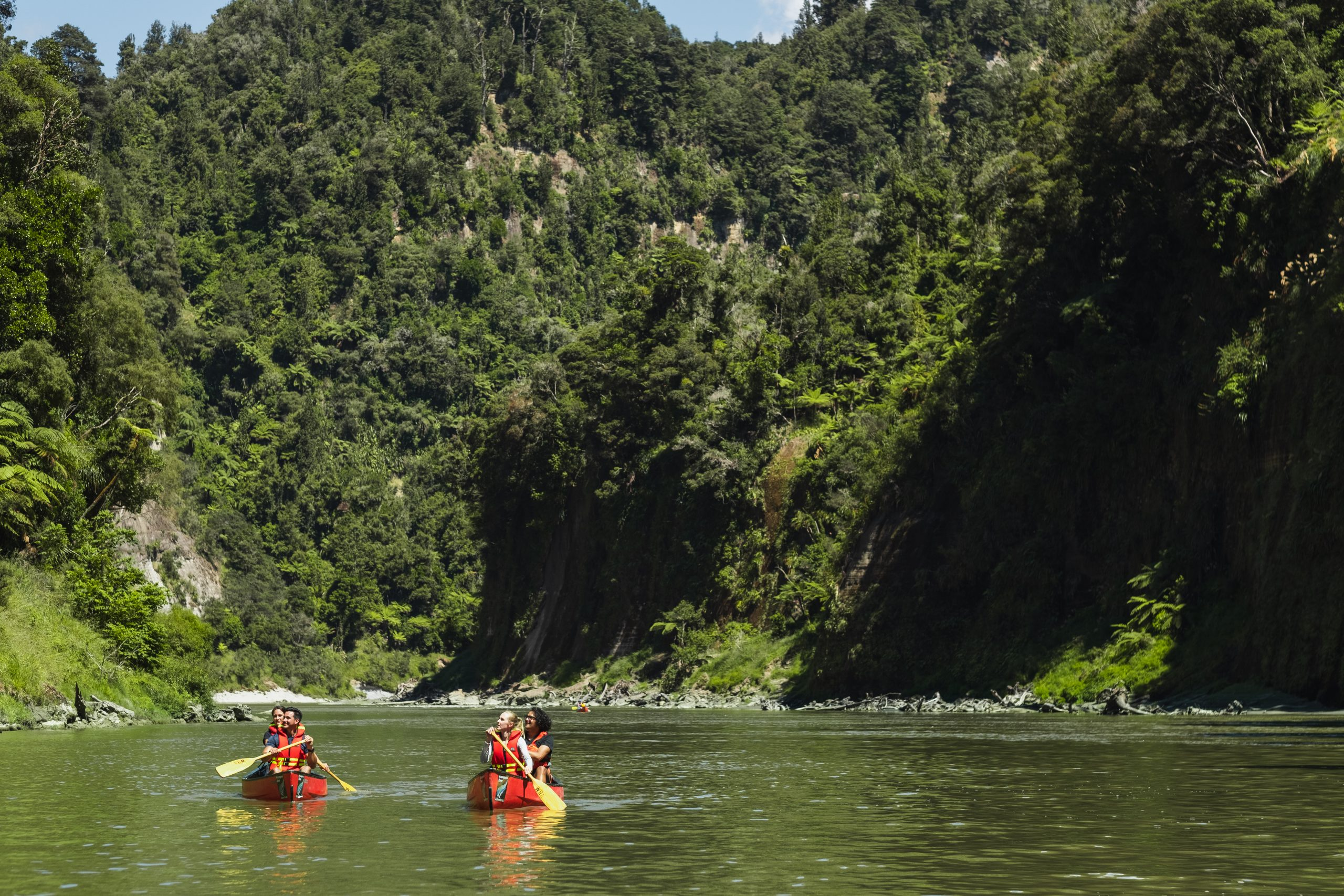 People in two canoes paddling down the Whanganui River